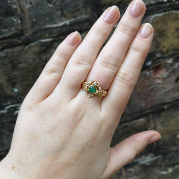 18k gold emerald claddagh on finger