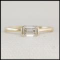 Minimalist engagement ring with emerald cut diamond