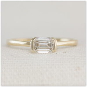 Minimalist engagement ring with emerald cut diamond