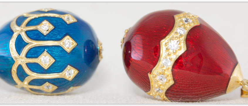 Two Beautiful Faberge Eggs. The First is painted using royal blue enamel and printed with fine 9k gold detailing. The second faberge egg is coated in a wonderful vivid red enamel and pained with a fine 9k gold design and set with zircon stones