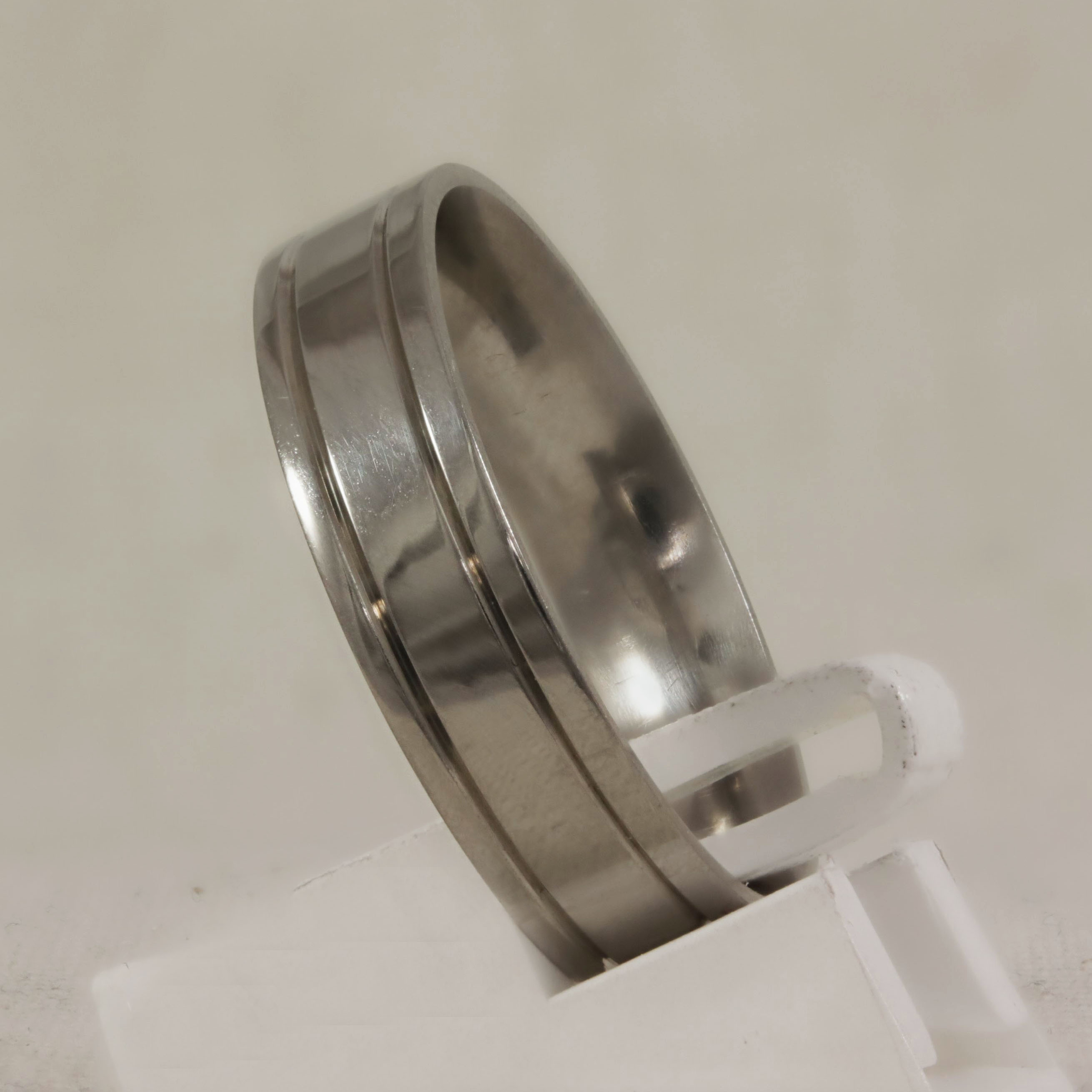 Flat band with track lines engraved each side. Finished with a high polish side