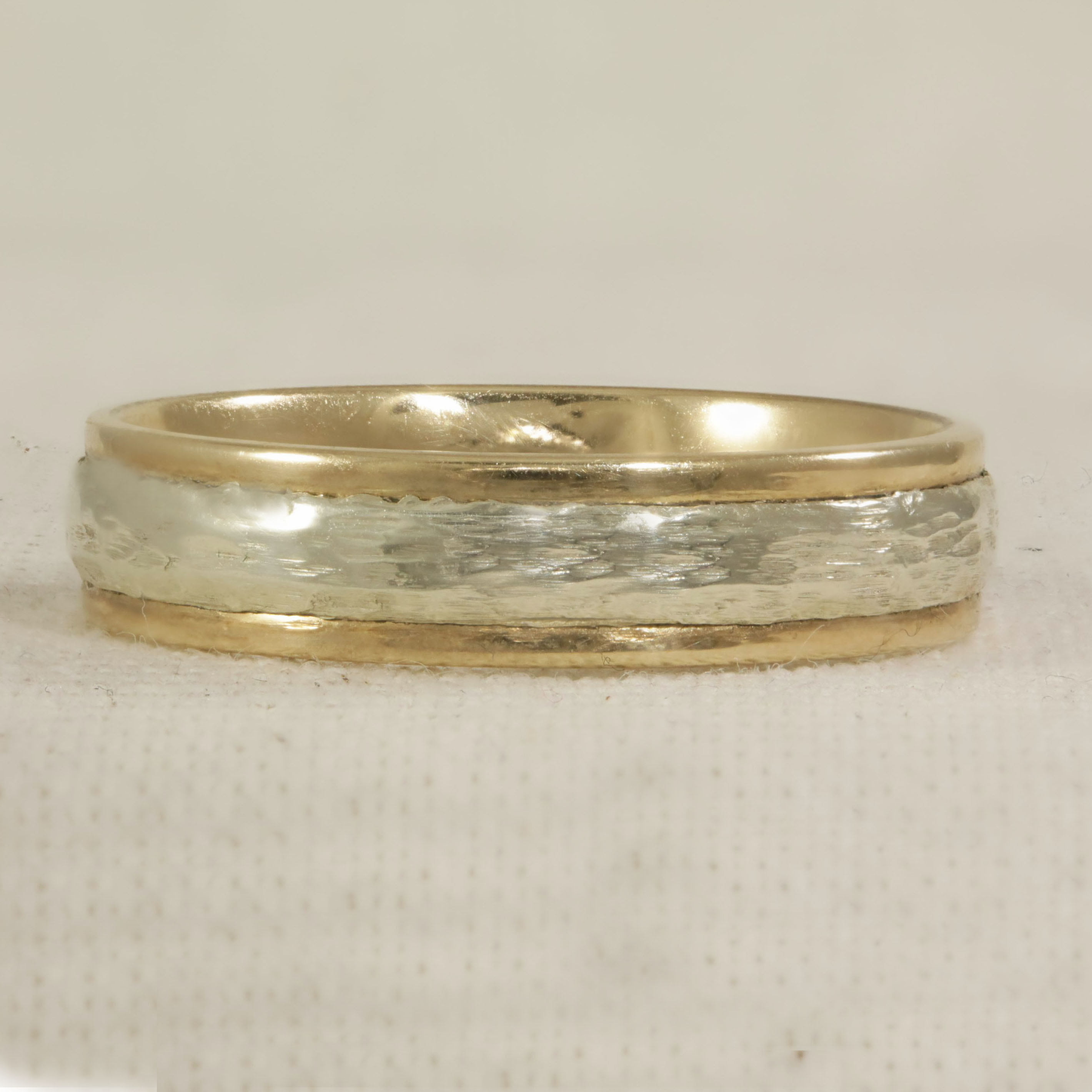 two tone court shaped ring, with bark effect centre.