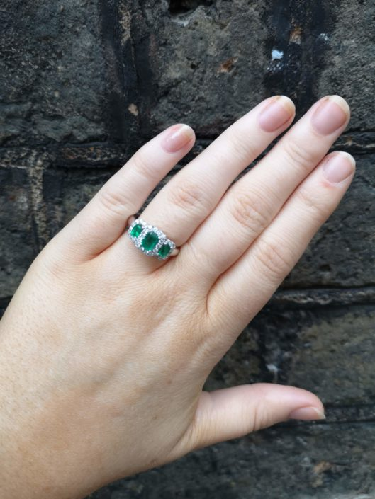 emerald and diamond three stone ring on a hand